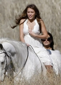 Miley Ray Cyrus in white on white horse